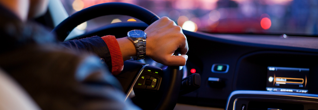 A man's hand on the steering wheel of his car