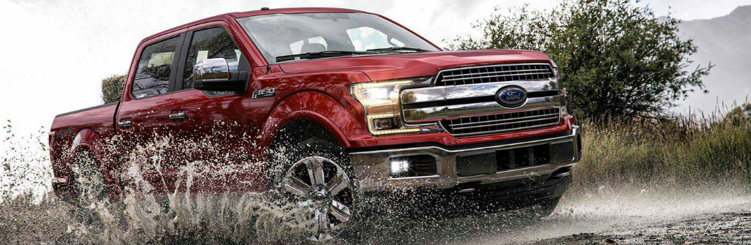 2018 Ford F-150 exterior shot with red color paint job driving across a muddy river