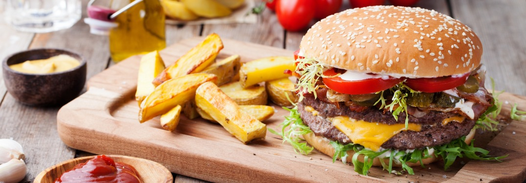 Burger and fries on wooden slab