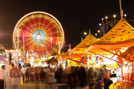 Ferris wheel and carnival rides lit up at night