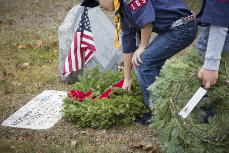 cout placing wreath next to grave site with American flag
