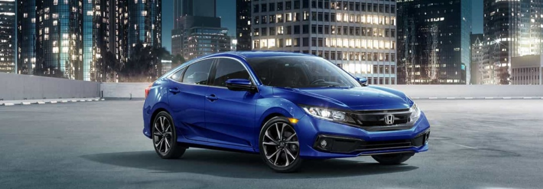 Side view of a blue 2019 Honda Civic parked in front of building at night