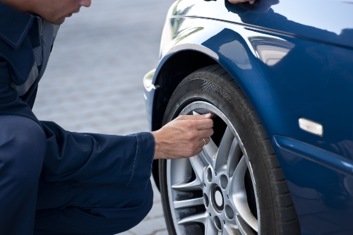 person checking tire inflation on vehicle