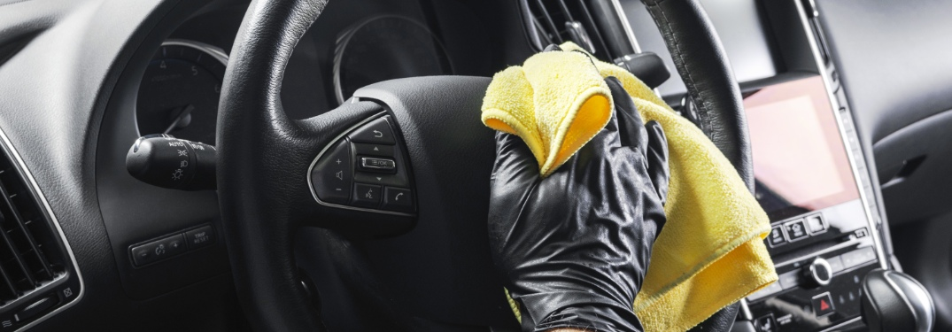 person cleaning a steering wheel