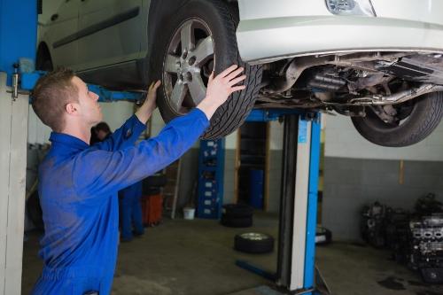mechanic examining tire on vehicle