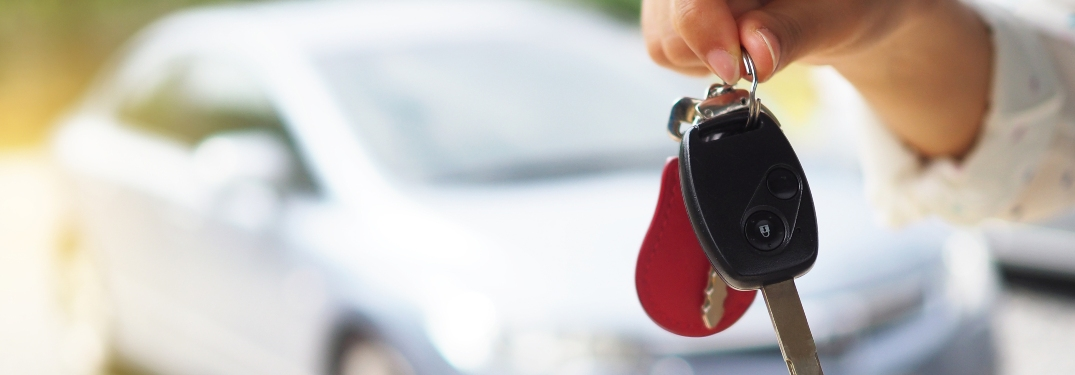 Person holding car keys in front of blurry vehicle