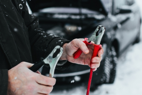 person holding jumper cables in front of stranded car