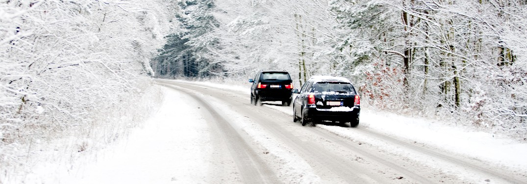 two cars driving on very snowy road