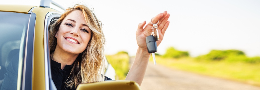 Smiling person leaning out car window while holding keys