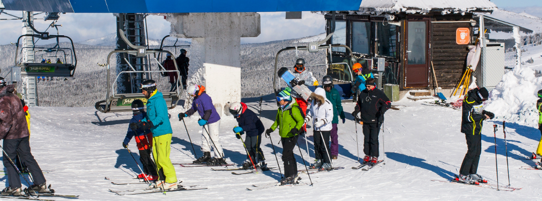 Group of People Getting Off the Ski Lift