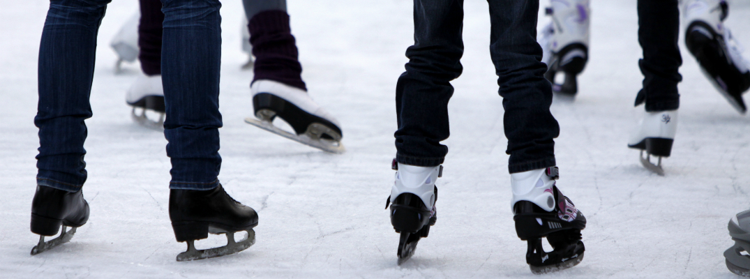 Group of People Pictured From the Legs Down Ice Skating