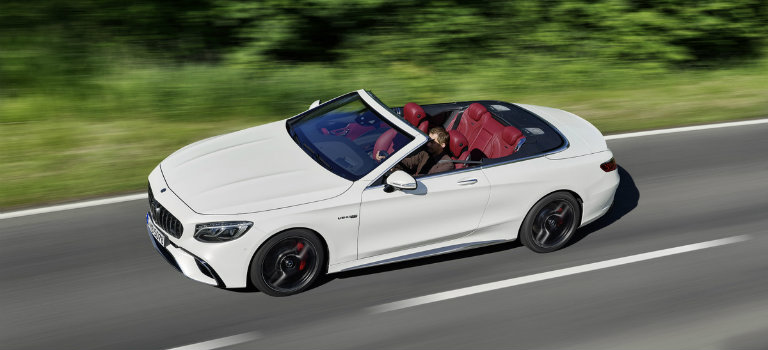 white 2018 Mercedes-Benz S-Class Cabriolet driving down the road with the top down