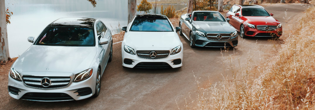 four models of the 2018 Mercedes-Benz E-Class lined up on a dirt path