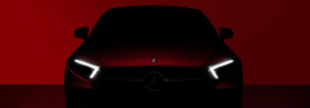 teaser image of the 2018 or 2019 Mercedes-Benz CLS with a dim red background and eye-catching v-shaped headlights