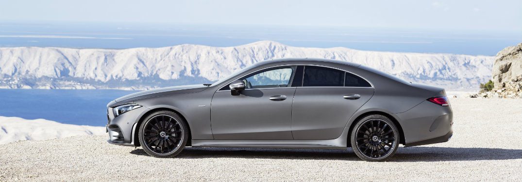side view of the 2019 Mercedes-Benz CLS with mountains and water in the background