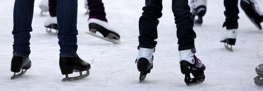 people ice skating, lower leg view