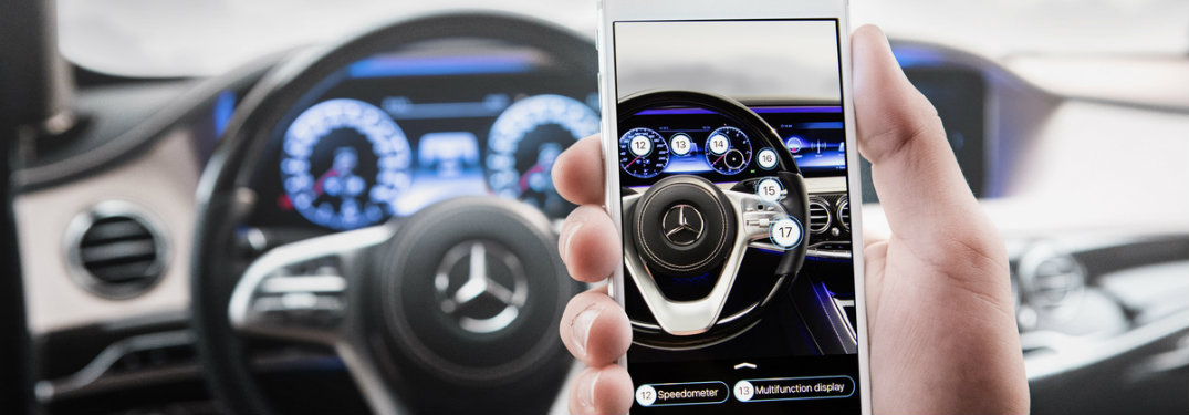 person using Ask Mercedes app to explore steering wheel features with virtual reality