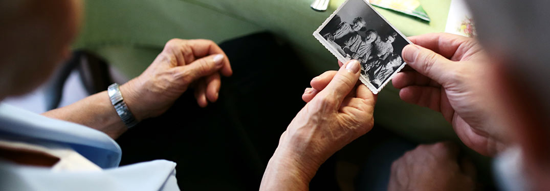 two people looking at an old photograph