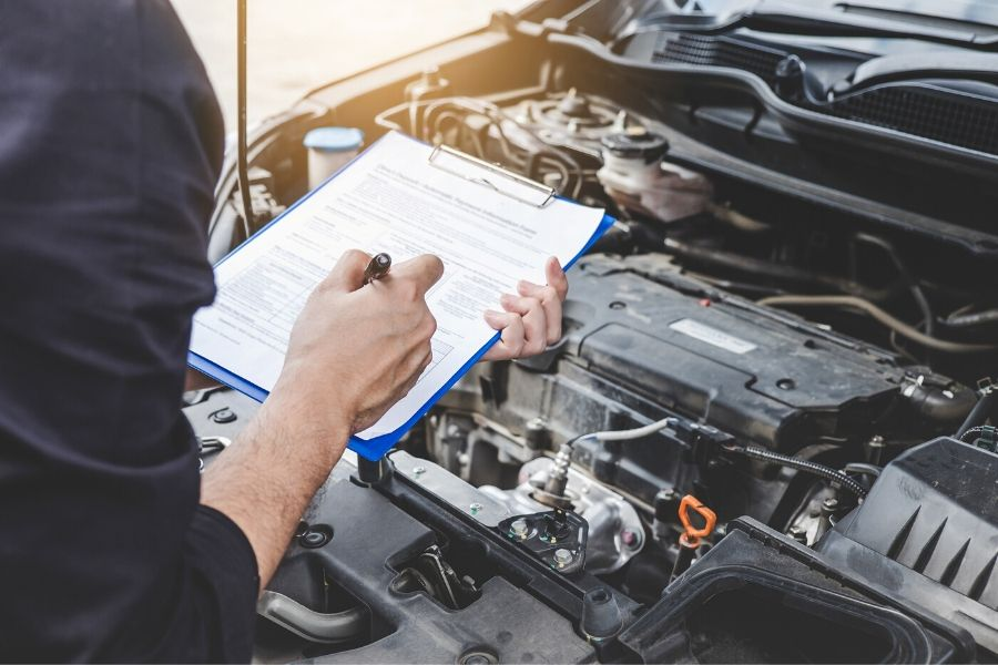 Mechanic checking off items on a list while inspecting engine