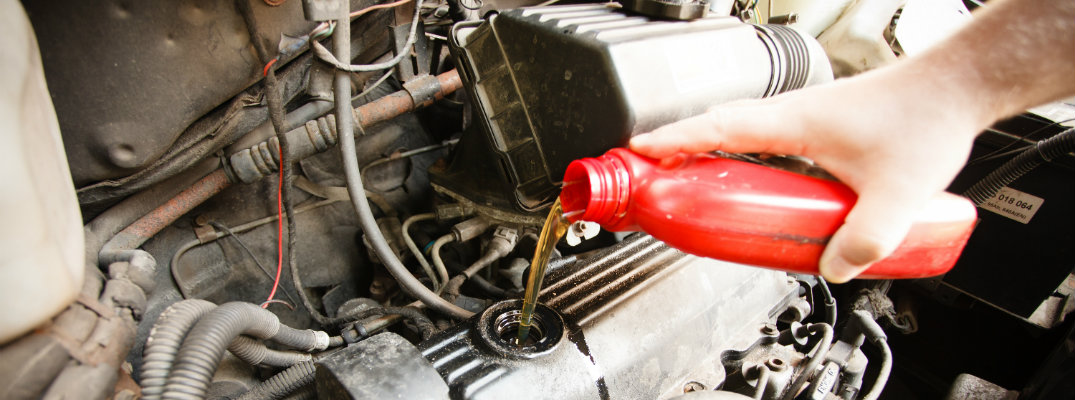 Man pouring engine oil in a car