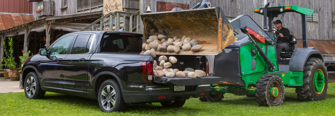 2018 Honda Ridgeline with rocks being dumped into its bed