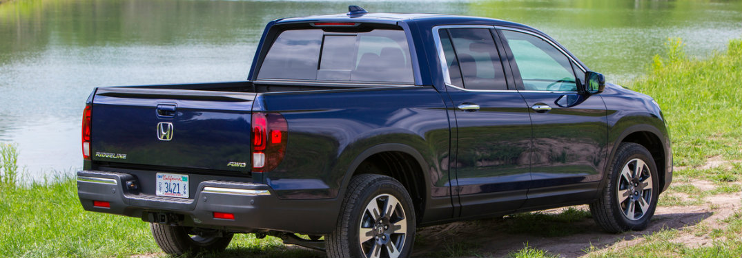 view of the rear of a 2018 Honda Ridgeline in blue by a lake
