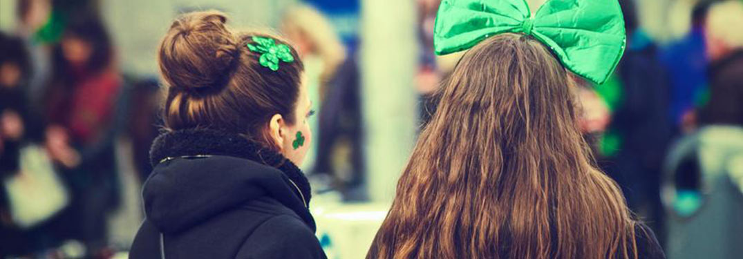 view of the back of the heads of two women with green bows in their hair for St. Patrick's Day