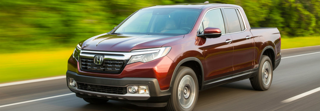 2019 Honda Ridgeline in dark red driving down the road