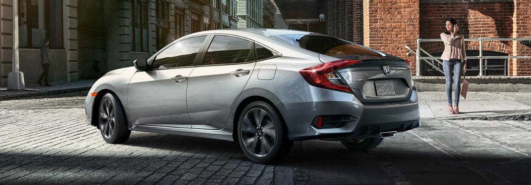 2019 Honda Civic Sedan exterior back fascia and drivers side with woman walking towards it