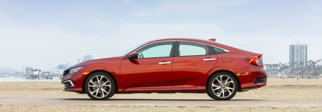 2019 Honda Civic exterior driver side profile in empty lot with city in background