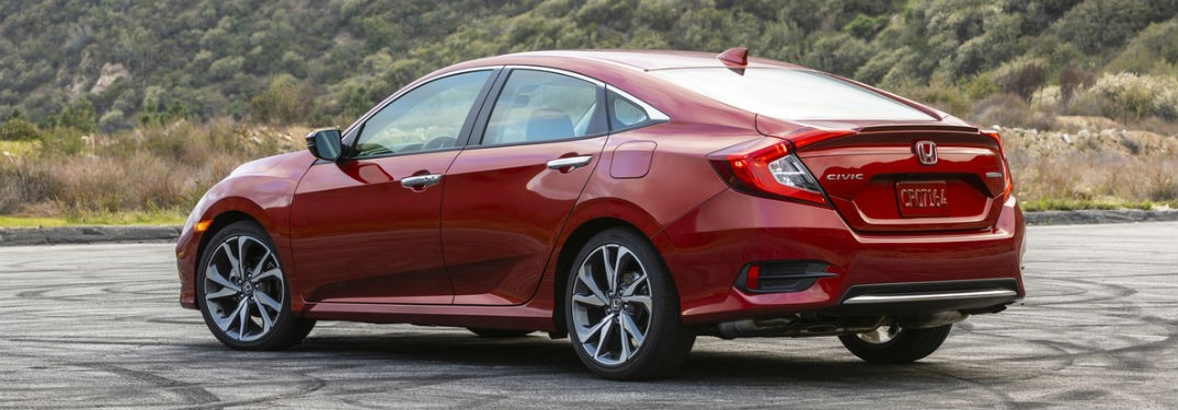 2019 Honda Civic exterior back fascia and driver side in empty lot with trees