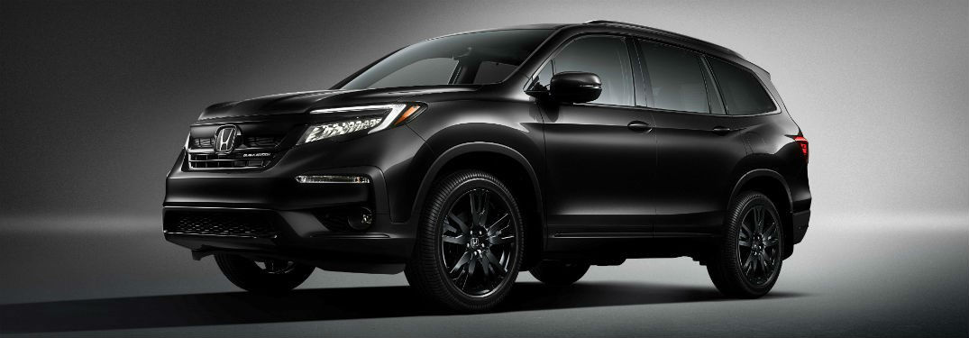 2020 Honda Pilot exterior front fascia and driver side in dark gray room with dramatic lighting