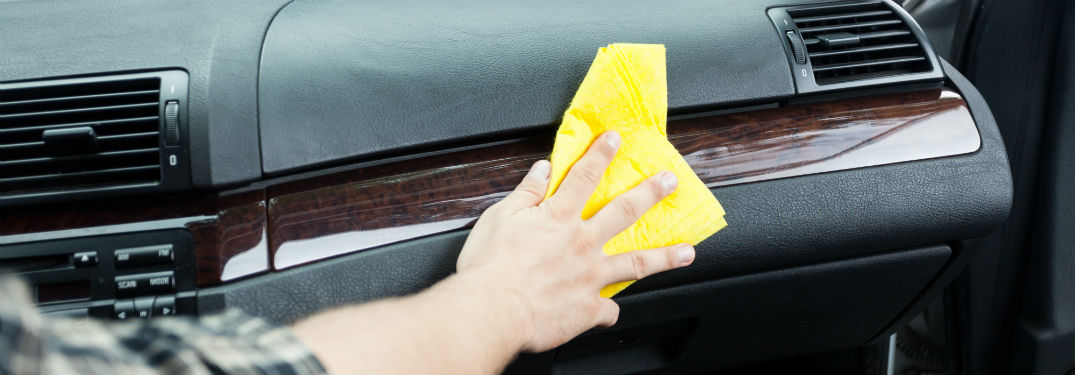 person wiping down dashboard in car