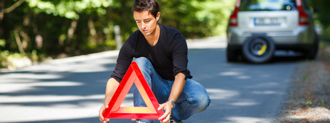 Man putting triangle reflector in road