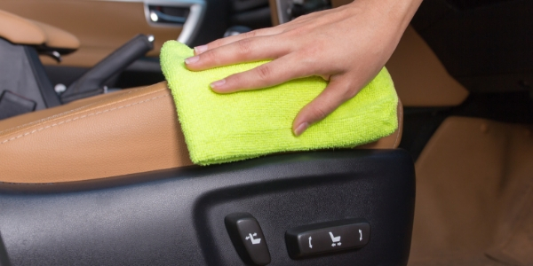 Closeup of hand cleaning vehicle interior with cloth