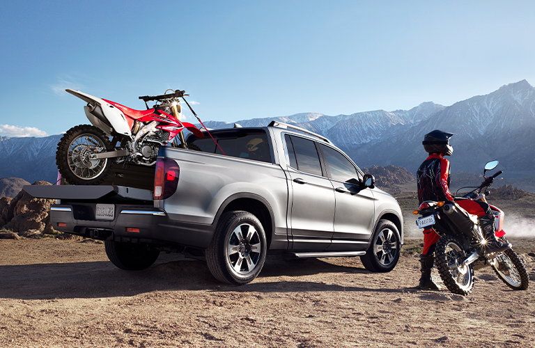 Silver 2020 Honda Ridgeline with dirt bike in truck bed