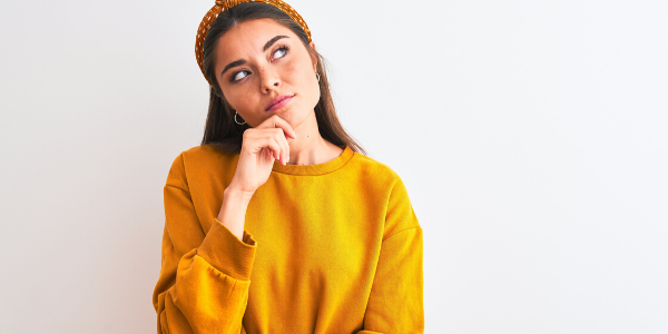 Girl in yellow sweater looking confused
