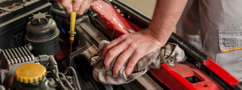 Closeup of mechanic working under hood of vehicle