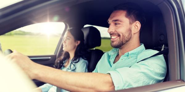 Man smiling in front seat of car