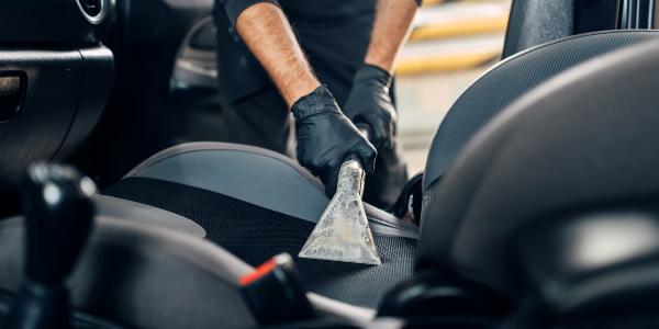 Mechanic vacuuming vehicle seat