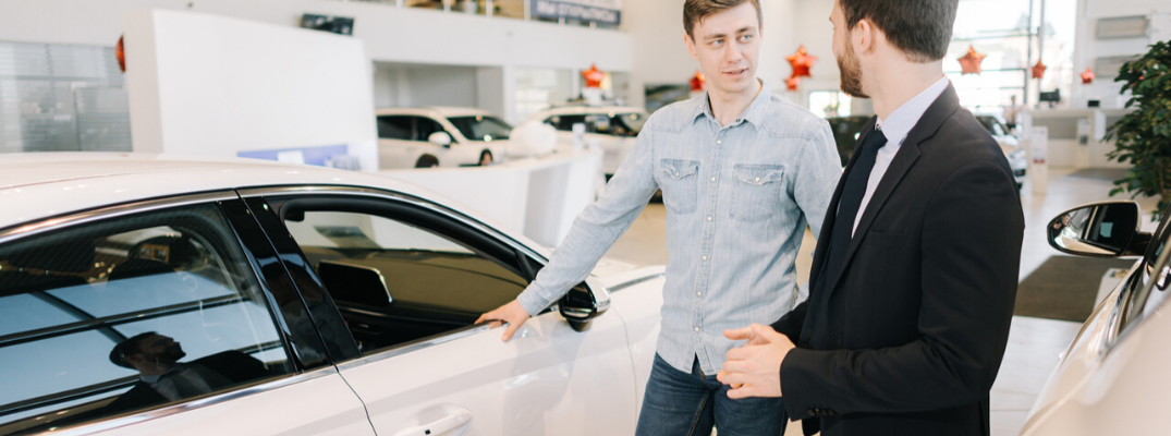 Two men talking in front of vehicle at dealership