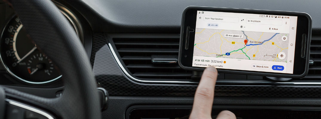 Finger pointing to smartphone with Google Maps on screen