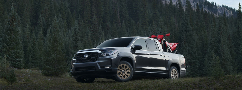 Black 2021 Honda Ridgeline with dirt bikes in truck bed