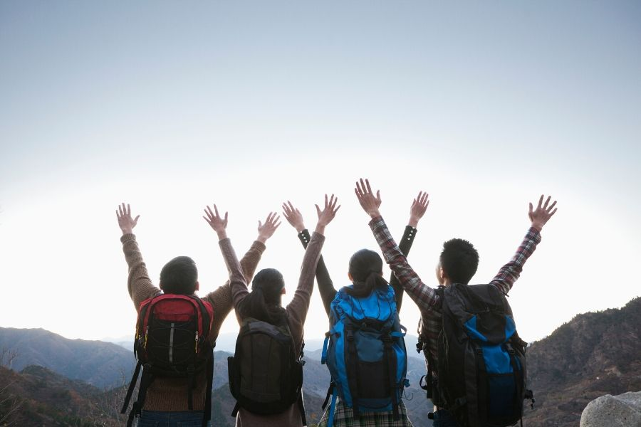 Four hikers with arms in the air