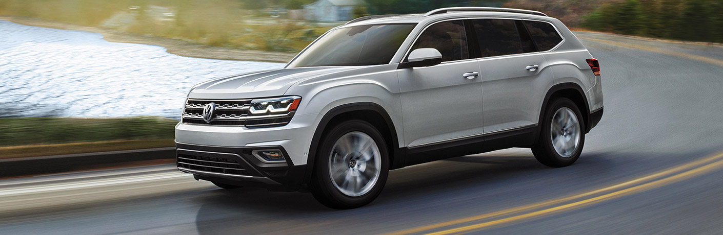 Exterior view of a silver 2019 Volkswagen Atlas driving down a two-lane highway