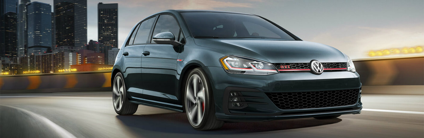 Exterior view of a teal 2019 Volkswagen Golf GTI driving down the highway