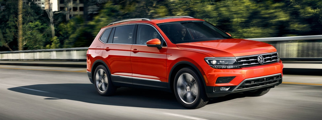 Exterior view of an orange 2019 Volkswagen Tiguan driving down a suburban street
