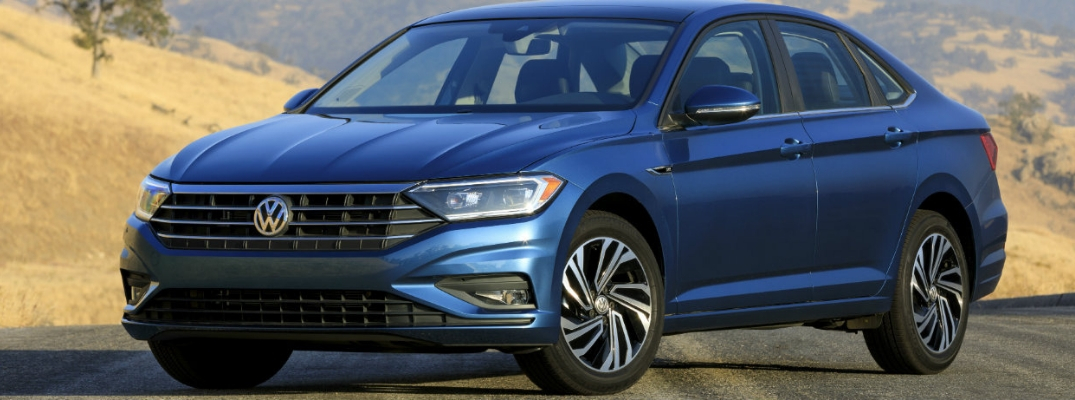 Exterior view of a blue 2019 Volkswagen Jetta parked in the middle of a country road