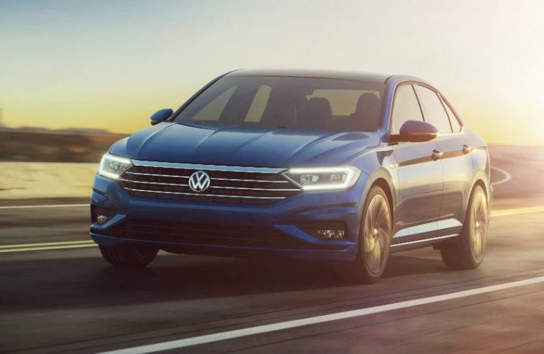 Exterior view of the front of a blue 2019 Volkswagen Jetta driving down a two-lane road