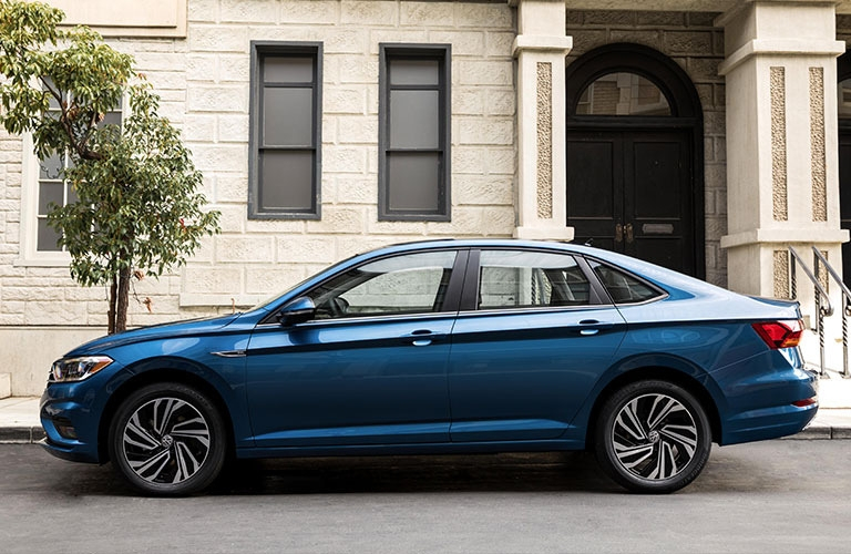 Exterior view of the driver's side of a blue 2019 Volkswagen Jetta parked on a city street